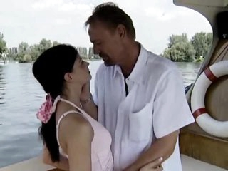 Gal in a pink dress sucks on a boat