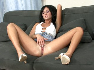 Raven haired babe Dora in short denim skirt spreads her legs on the couch to play withe her bare snatch right in front of you. She loves to stroke her thirsty pussy on camera.