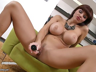 Playful pornstar Aletta Ocean with breathtaking monster tits and tigth ass bares it all flirtatiously. Then she opens her legs and takes dildo in her sexy neat pussy in green armchair.